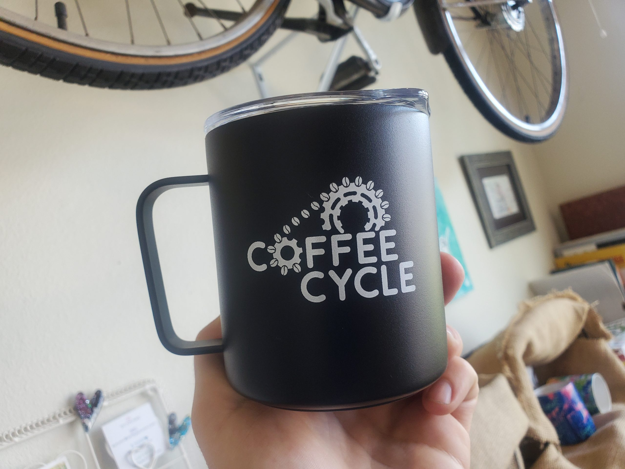 Coffee Cycle Camp Mug in front of a bicycle being held up in front of the camera.