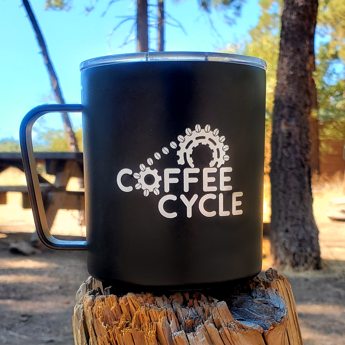 A black stainless steel camp mug with the coffee cycle logo in white.
